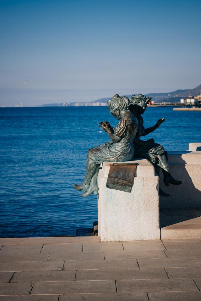 Скульптуру установили в 2004 году в честь годовщины возвращения Триеста в состав Италии. Две девушки шьют итальянский флаг